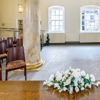 A table with flowers on it. The table is on a titled floor, and has rows of chairs and a colum next to it.