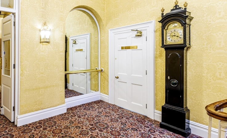 A small room with a wall-length mirror, door and grandfather clock.
