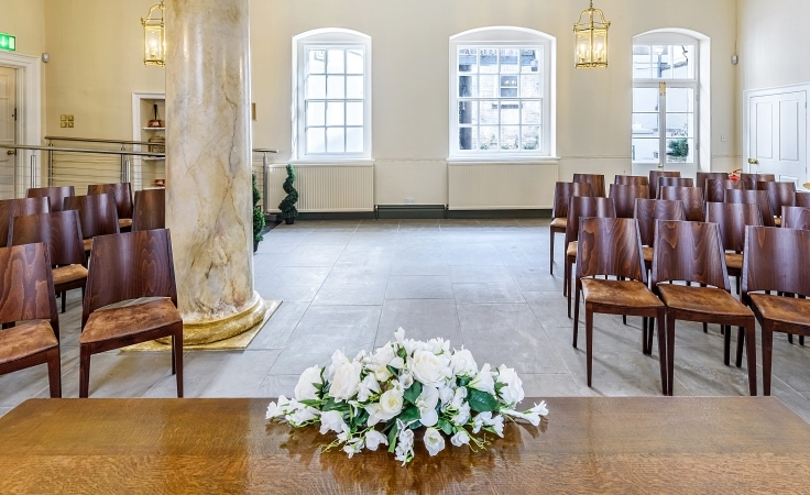 A room with chairs, a column, a tiled floor and flowers on a table.