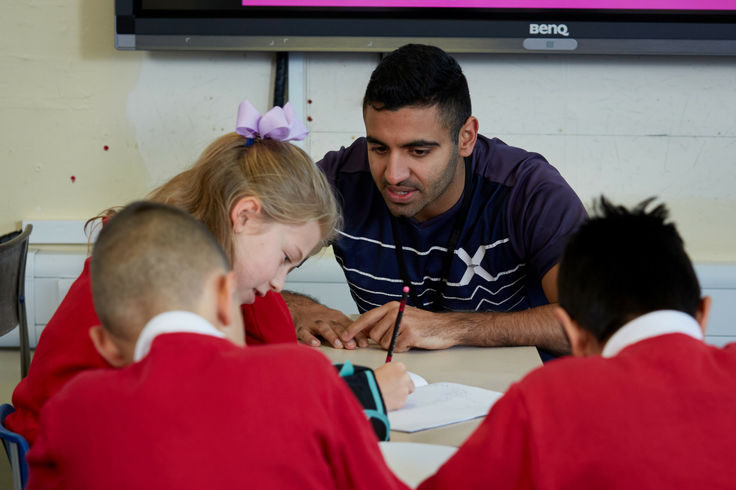 A teacher helping a school child with her Maths work.