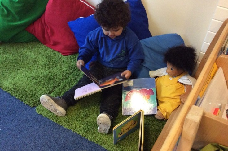 Young child reading at the Seedlings Group