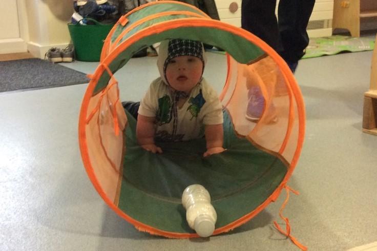 baby crawling through tunnel