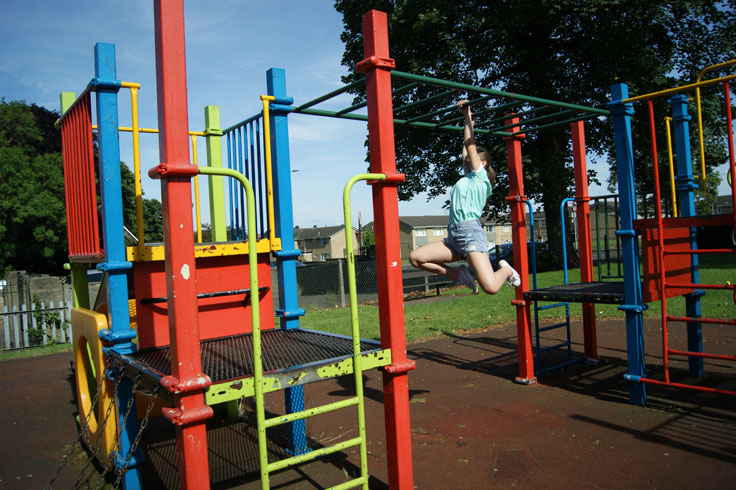 A girl on the monkey bars in a play area.
