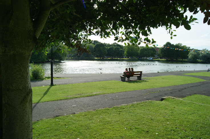 A group of people sat on a bench in front of a boating lake.