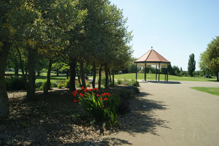 A wildflower bed with people on a bench behind it, and a bandstand on the right.