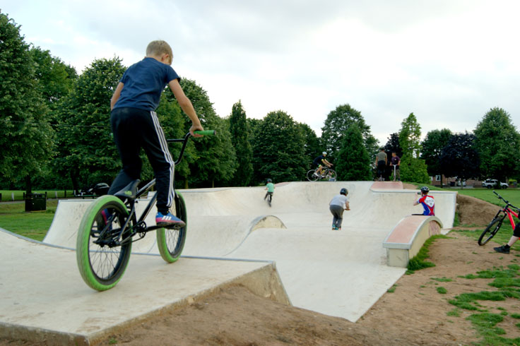 A group of children on bikes and scooters riding up and down bike ramps.