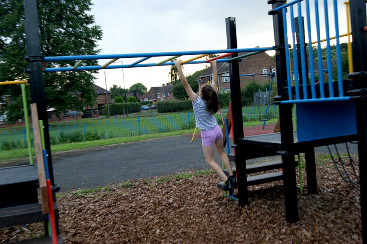 A girl swinging on monkey bars in a play area.