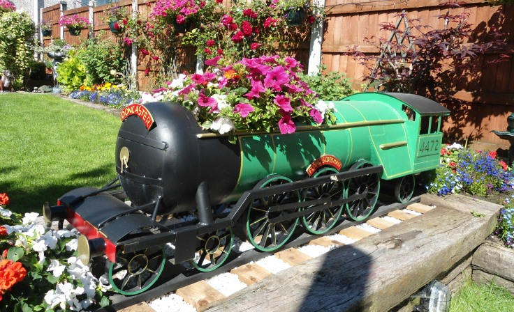 A large model train covered in flowers