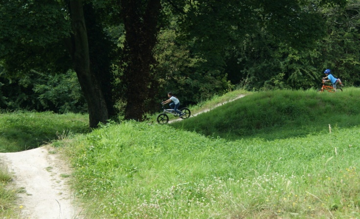 Two children on bikes riding on a BMX track.