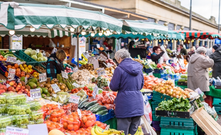 Customers looking at fruit and veg for sale whilst stall holders are selling it to them
