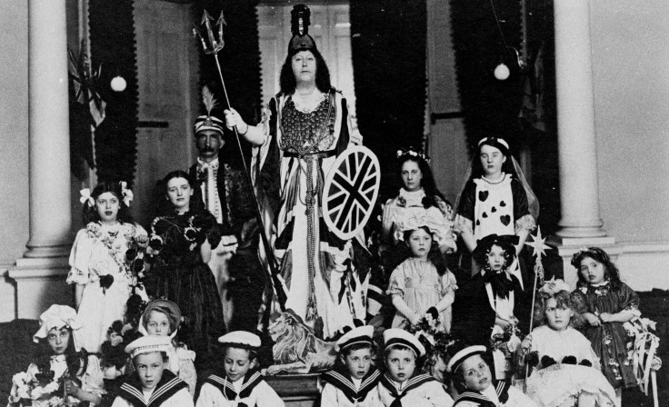 A group of children and young peopled dressed in costume, who are seated and stood in front of a woman in costume