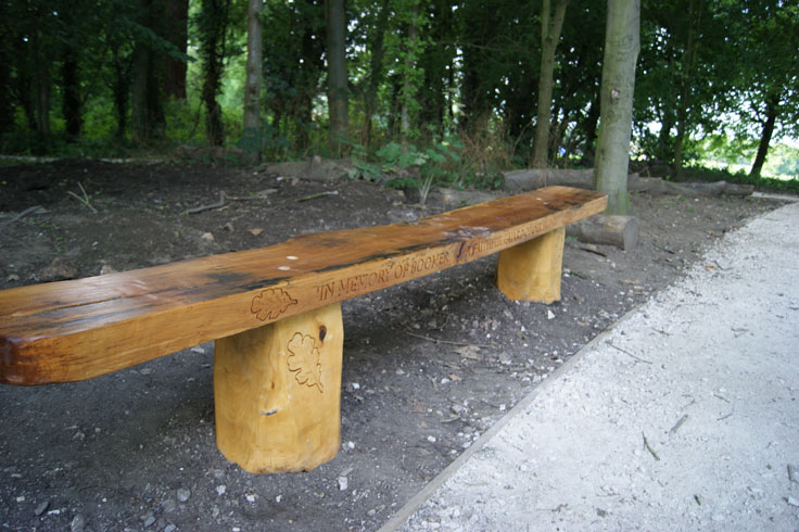 A memorial bench with 'in memory of boomer' inscribed on it.