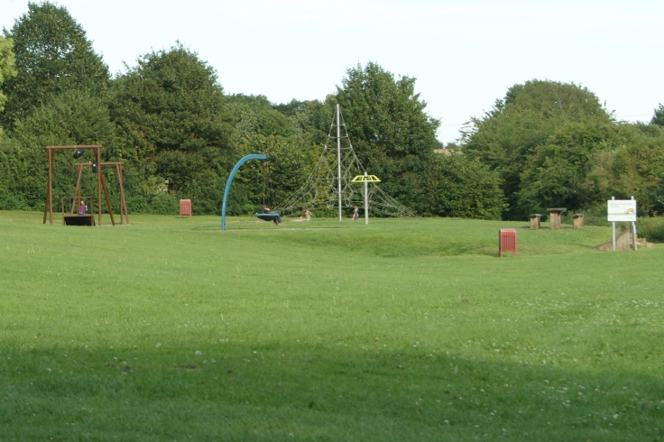 A park with a play area, bench, picnic area, bin and a sign for the play area.