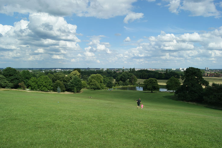 Two people running down a hill towards a lake, with other people sat on the hill.