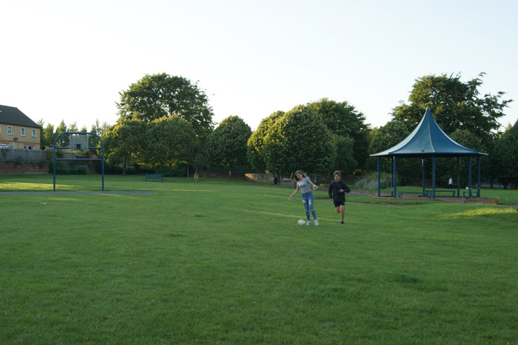 Young people playing football in a park, with a bandstand on their right.