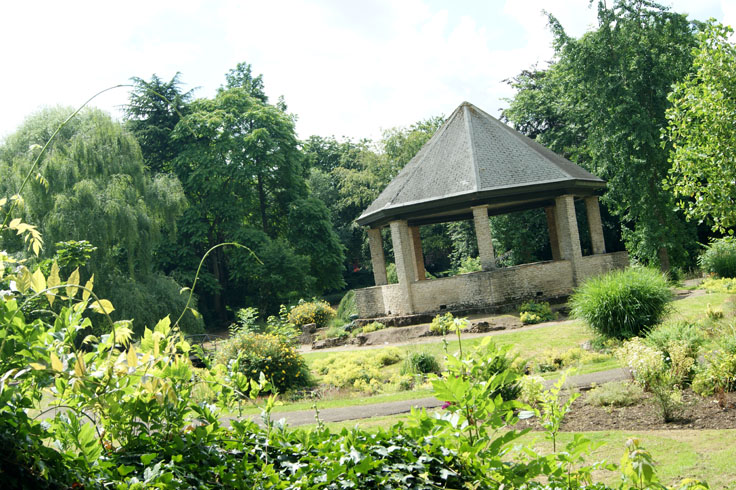 A park garden with a bandstand in the middle.