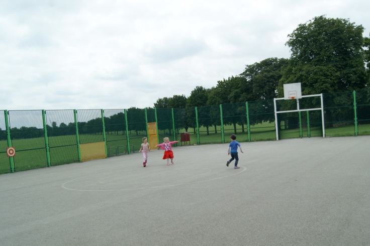 A group of kids playing in a multi-use games area.
