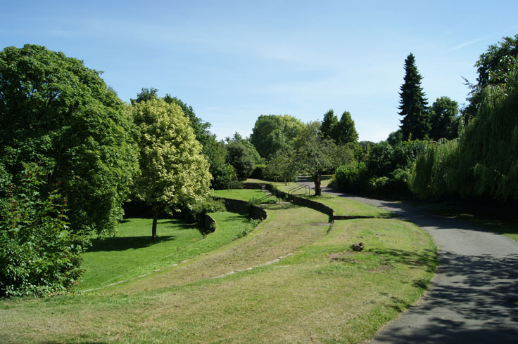 A path with trees all around it, and tiered levels on the left.