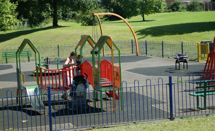 A woman and a child playing in a play area.