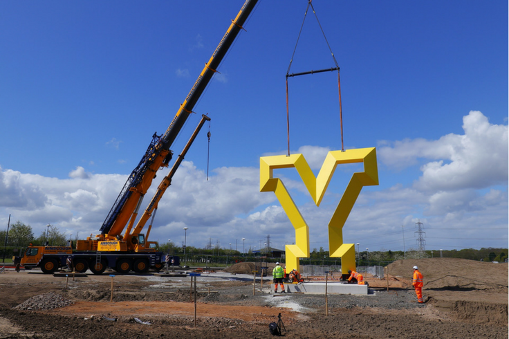 A yellow Y statue being installed.