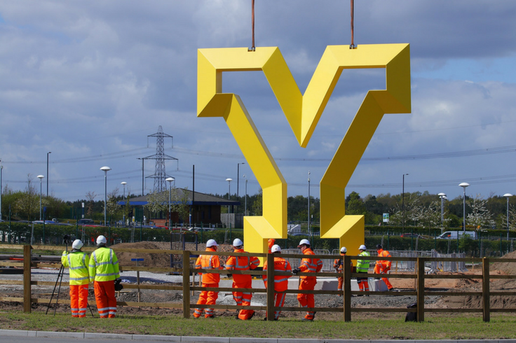 A group of construction workers stood in front of a yellow Y statue.