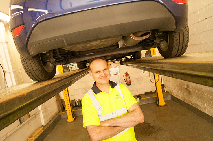 Vehicle tester stood in a testing pit under a car on ramp.
